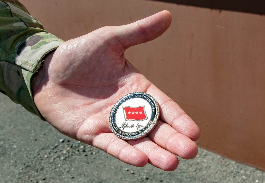 U.S. Air Force Senior Master Sgt. Corydon Coombs, Defense Threat Reduction Agency courier, displays the coin presented to him by U.S. Army Gen.l Steve Lyons, U.S. Transportation Command commander, Scott Air Force Base, Illinois, during a visit to the 60th Aerial Port Squadron warehouse, July 24, 2019 at Travis Air Force Base, California. Lyons had the opportunity to interact with Travis Airmen and tour several units while on the base visit. (U.S. Air Force photo by Heide Couch