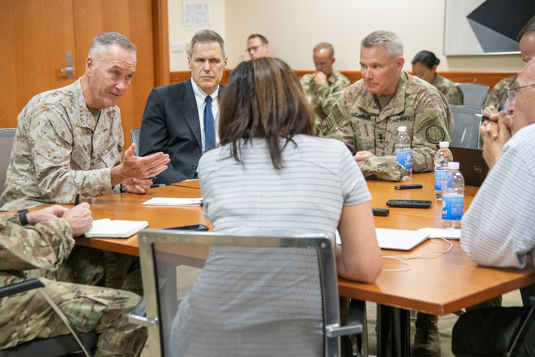 Military leaders and media members talk around a table.