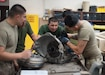 Members of the Armed Forces from the Republic of Kazakhstan and the Arizona Army National Guard dismantle the transmission from a M998A2 Series High Mobility Multipurpose Wheeled Vehicle (HMMWV) during a State Partnership Program vehicle maintenance exchange at the Papago Park Military Reservation July 16. During this week-long maintenance exchange, wheeled vehicle mechanics from both countries explained how they conduct fleet maintenance operations, parts and tools supply logistics and manage personnel and facilities that support maintenance functions.