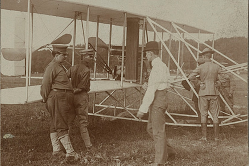 Six men in early 1900s garb stand in a field beside the earliest model of a military airplane.