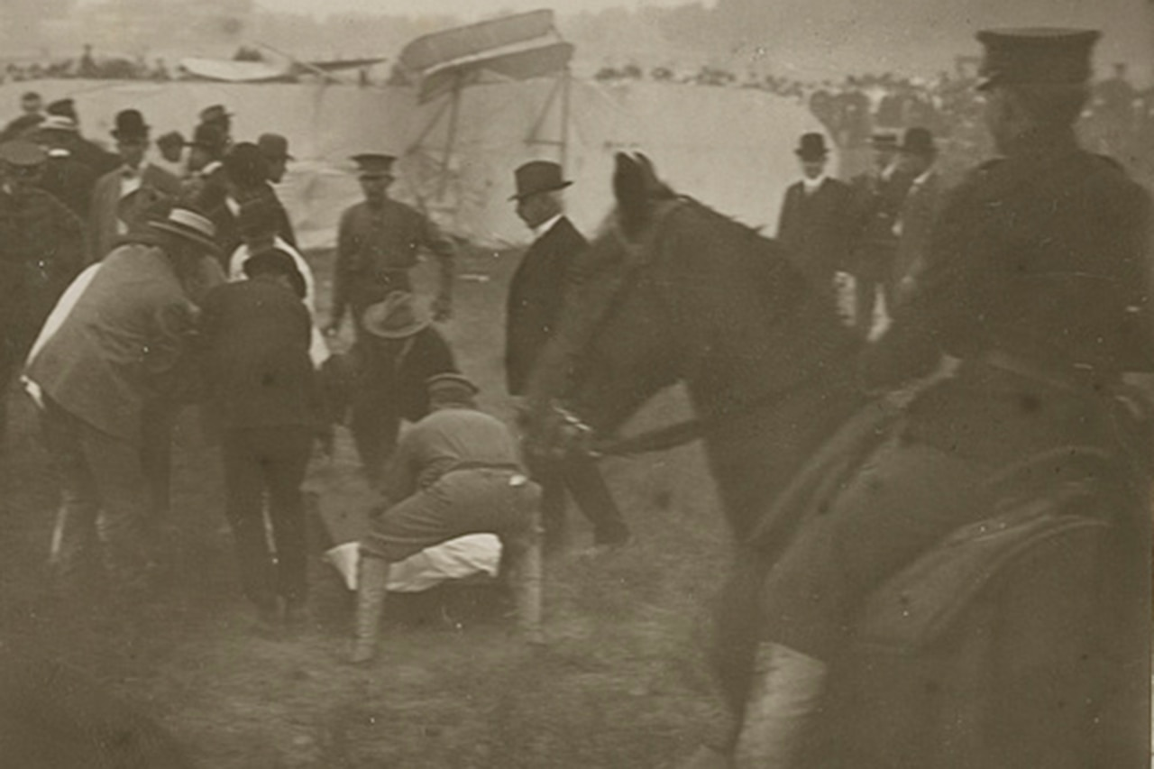 Several people work to put a man on a stretcher in a field with a crashed airplane on its side in the background. A soldier on a horse is in the foreground.