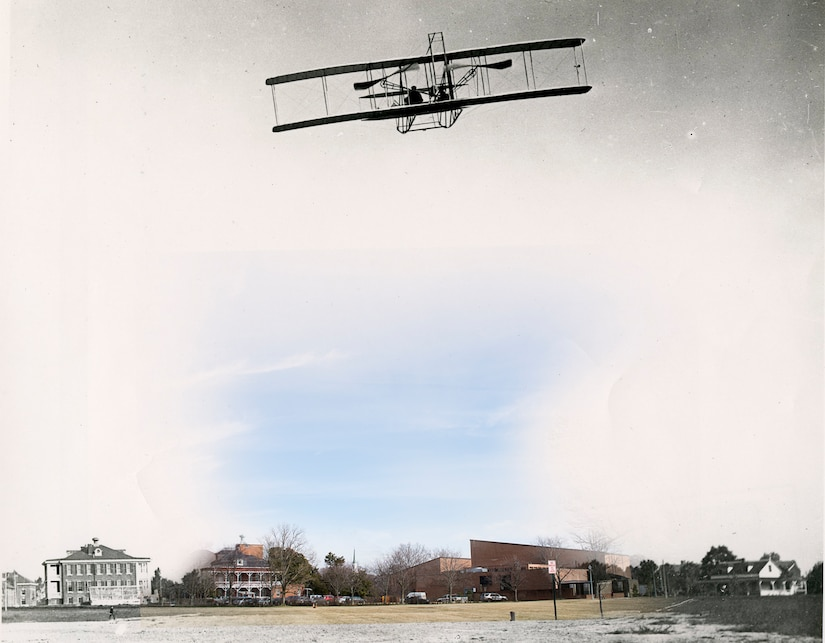 A Wright Military Flyer airplane flies in the skies above a field with buildings in the background.