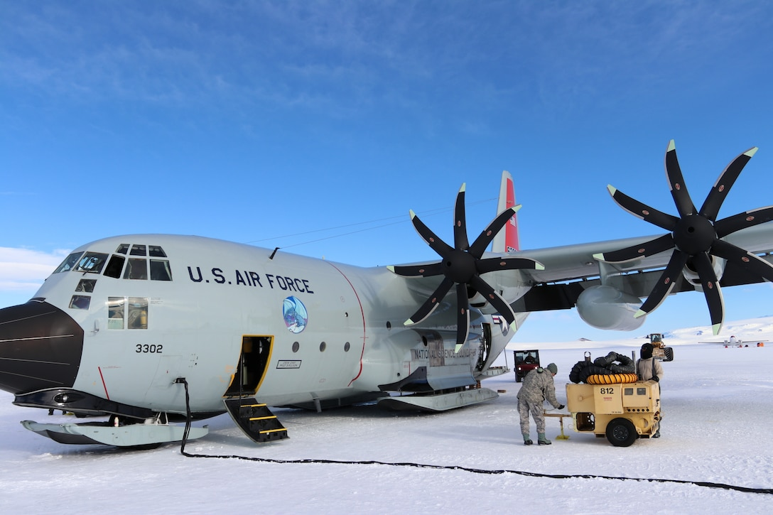 An Air Force LC-130 cargo plane with skis sits on a snow-covered runway. A line for fuel is attached to it, and two men work on a piece of equipment nearby.