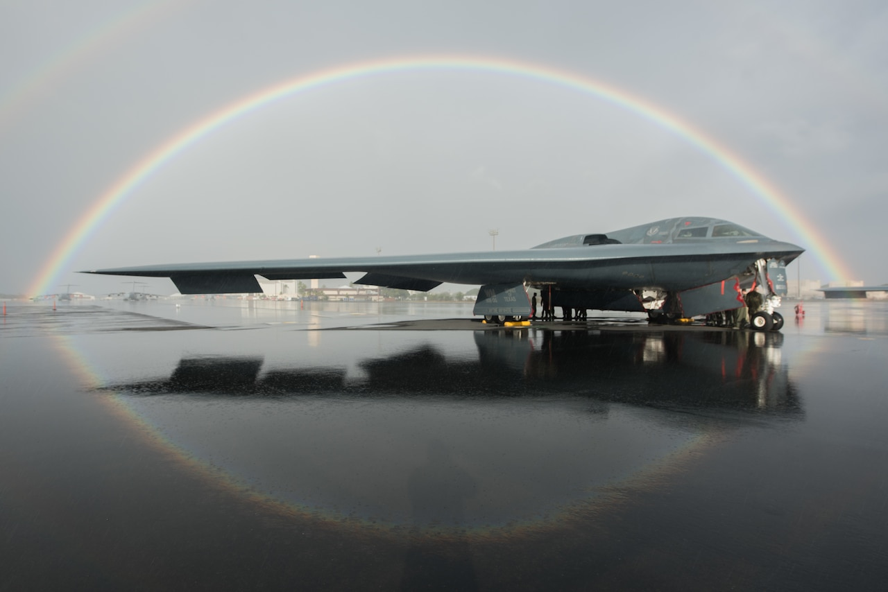A B-2 Spirit bomber sits on the flight line in Hawaii. A rainbow encircles it.