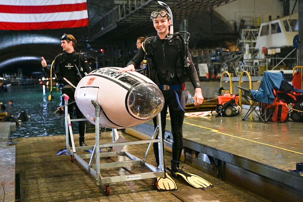 A student poses next to a human-powered submarine.