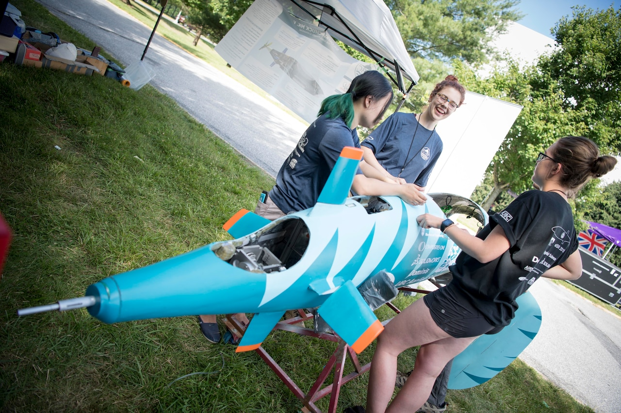 Students perform maintenance on their human-powered submarine.