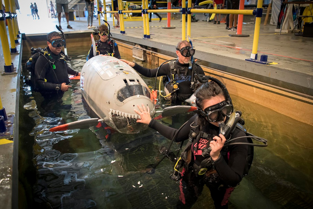 Students lower their human-powered submarine into the water.