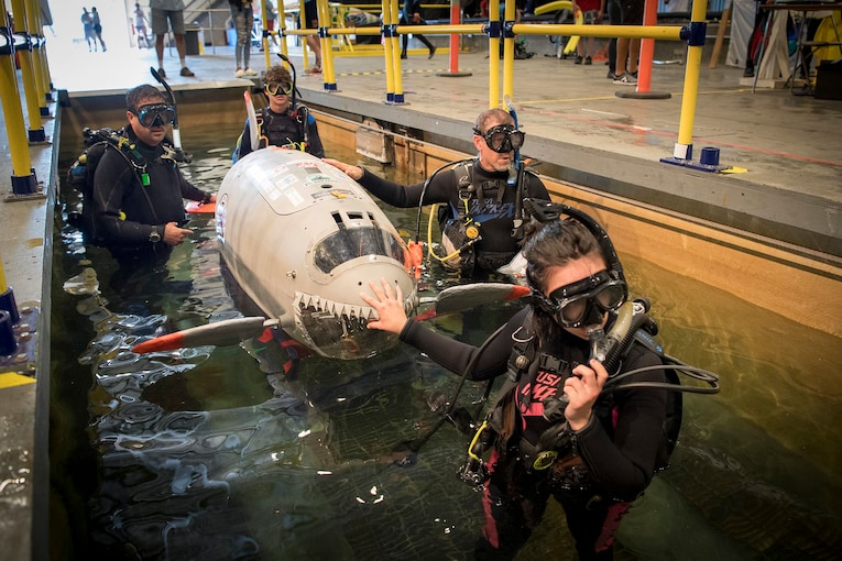 Several people work on a submarine built by students.