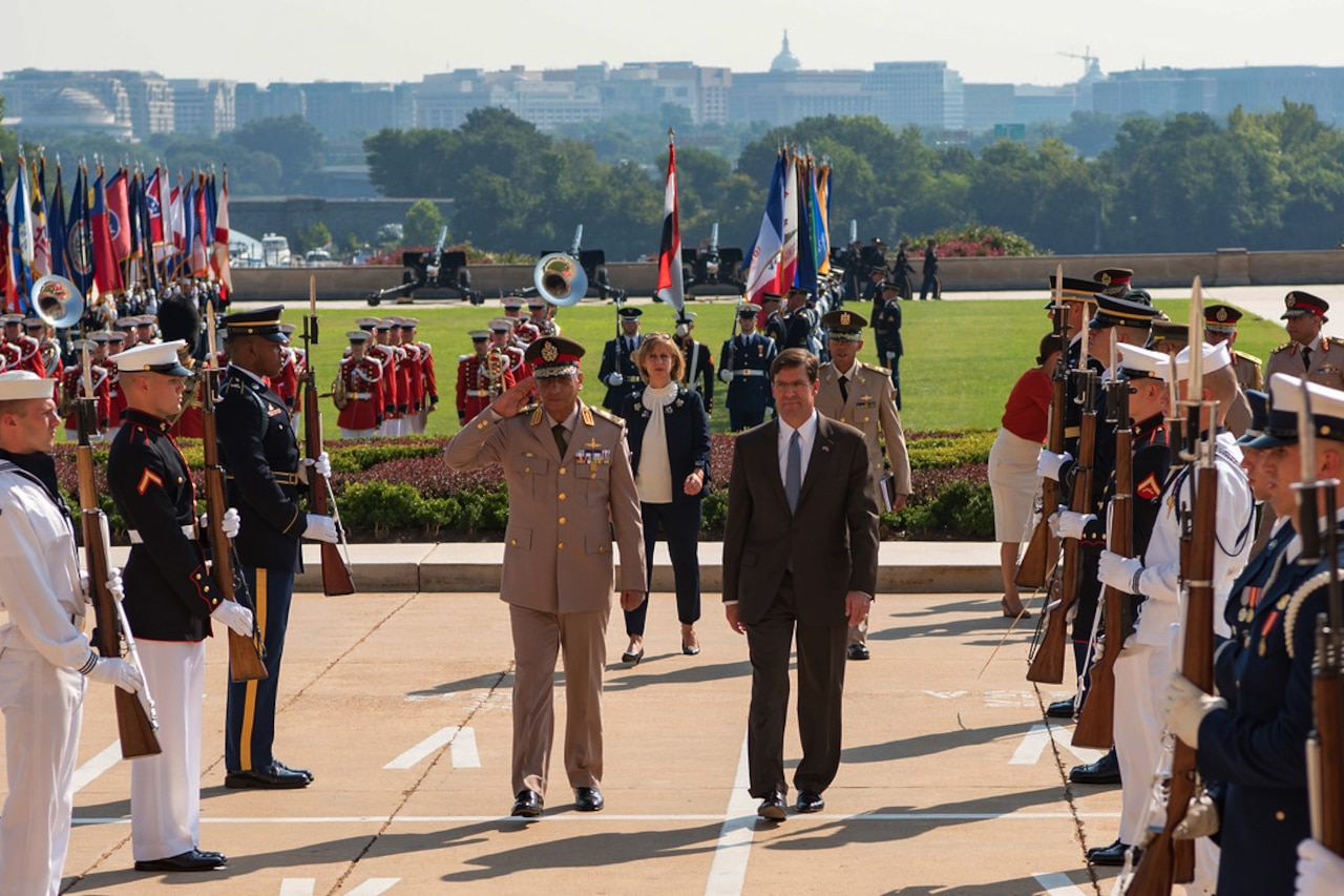 Officials walk up the walkway to the Pentagon.