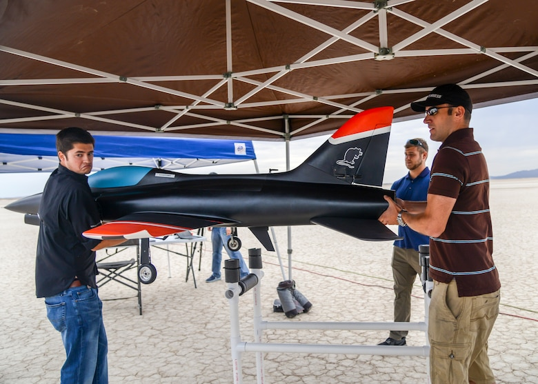 Engineers lift an unmanned jet-powered aircraft into position for a flight test at Edwards Air Force Base, Calif., July 25. (U.S. Air Force photo by Giancarlo Casem)