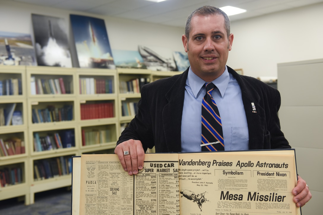 """Scott Bailey, 30th Space Wing historian, showcases an archived July 1969 issue of the """"Mesa Missilier"""", a publication which served as base newspaper during the Apollo 11 lunar mission. Utilizing publications like this in the 30th SW history archive, Bailey is able to take the Wing's past legacy of accomplishment and tie it to current and future operations and the mission of the Wing. (U.S. Air Force photo by Michael Peterson)"""