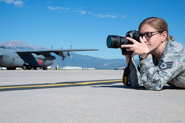 Staff Sgt. Heather Heiney, a 302nd Airlift Wing photojournalist, takes photos on the flight line at Peterson Air Force Base, Colorado, July 3, 2019. (U.S. Air Force photo by Tech. Sgt. Frank Casciotta)
