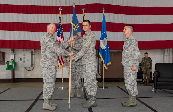 U.S. Air Force Col. Timothy Trimmell, 52nd Maintenance Group commander, left, gives the ceremonial guidon to Lt. Col. Brian Scozzaro, incoming 52nd Aircraft Maintenance Squadron commander, during the 52nd AMXS Change of Command Ceremony at Spangdahlem Air Base, Germany, July 26, 2019. (U.S. Air Force photo by Airman 1st Class Kyle Cope)