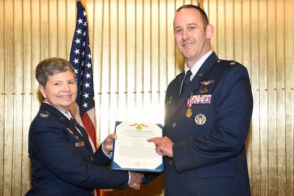 Col Heidi Paulson presents Mr. Brian Kucharski with the Meritorious Civilian Service award. (U.S. Air Force photo by Staff Sgt. Alexandra M. Longfellow)