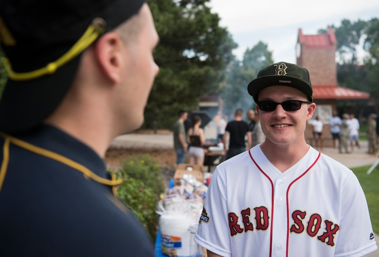 Airman 1st Class Phillippe Breault, 50th Operations Support Squadron student, talks with another Airman during the inaugural Junior Enlisted Airmen Summer Barbeque at Peterson Air Force Base, Colorado, July 26, 2019. The event featured free food, games and a basket raffle. (U.S. Air Force photo by Airman 1st Class Jonathan Whitely)