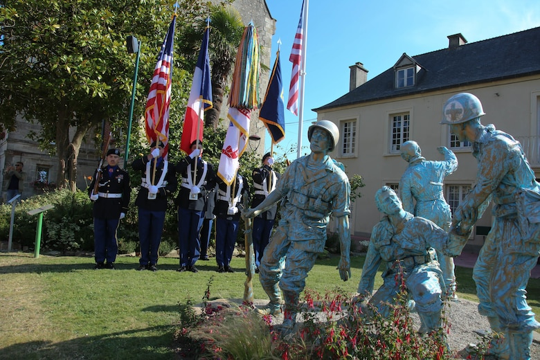 Color Guard Soldiers assigned to the 7th Mission Support Command stand in front of the Four Braves Memorial in Periers, France during the 75th Anniversary of the liberation of the town on July 27, 2019. The 90th Infantry Division, now the 90th Sustainment Brigade, liberated the town during World War II seven weeks after landing on Utah beach just 35 kilometers away. (U.S. Army Reserve Photo by Capt. Joe Bush)