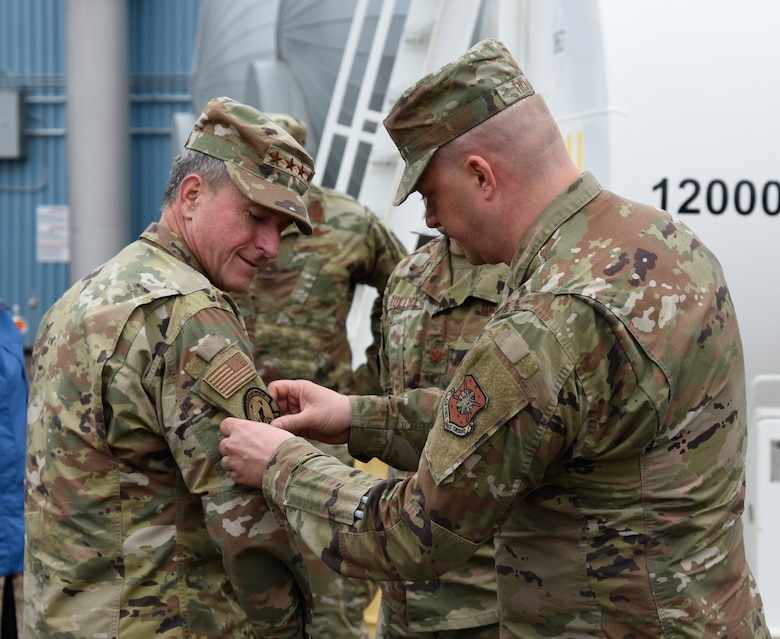 Master Sgt. Timothy Tichawa, 821st Air Base Group member, placed a 12th Space Warning Squadron patch on the Air Force Chief of Staff General David Goldfein's uniform during a site visit to Thule Air Base, Greenland, July 20, 2019. The squadron is one of three Ballistic Missile Early Warning System radar stations which collectively track satellites, missiles and other objects moving in the airspace above the North Pole. (U.S. Air Force photo by Staff Sgt. Alexandra M. Longfellow)