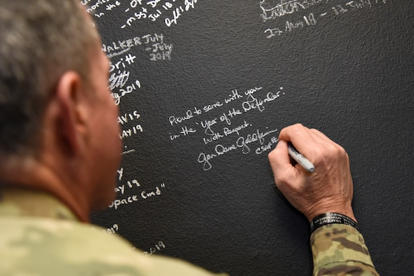 The 21st Air Force Chief of Staff David Goldfein, signs the 821st Security Forces Squadron's Defender wall during his visit to Thule Air Base, Greenland July 20, 2019. Thule AB was the last stop of a 10-day visit with allies and partners in Europe including Estonia, Finland, United Kingdom, Germany and Greenland. (U.S. Air Force photo by Staff Sgt. Alexandra M. Longfellow)