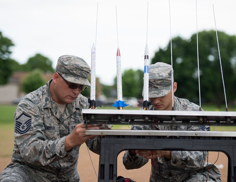 U.S. Air Force Master Sgt. Jeremy Bundgard, 133rd Logistics Readiness Squadron, left, and Senior Airman Geoffrey Slaughter, 133rd Aircraft Maintenance Squadron, attach wires to the rockets in St. Paul, Minn., July 18, 2019.