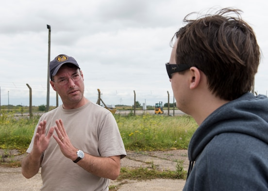 Paul George Bellamy, Airfield Research Group director of archives and collections, explains to Christopher Klimovitz the historical significance of this location on the former flight line near the Alconbury Airfield Heritage Collection, England, July 14, 2019. In the 1960's and 1970's this location was used as a Photographic Processing and Interpretation Facility for processing reconnaissance photos gathered from RF4C Phantom aircrafts. (U.S. Air Force photo by Airman 1st Class Jennifer Zima)