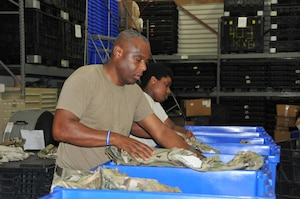 Senior Master Sgt. Anthony Brown, 403rd Logisitics Readiness Squadron logistics supply manager, and Airman Basic Damaja Prince, 403rd LRS supply apprentice, separate the new Operational Camouflage Pattern uniforms by size in order to fill uniform orders as required. The new uniforms will be mandatory wear by April 1, 2021, with deploying members being the first to receive the uniform. (U.S. Air Force photo by Jessica L. Kendziorek)