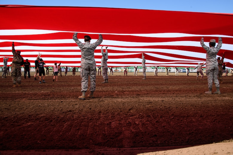 Hill Air Force Base Airmen alongside other military members and first responders serving in Utah unfurl an American flag during Patriot Night at the Ogden Pioneer Days Rodeo in Ogden, Utah, July 22, 2019.