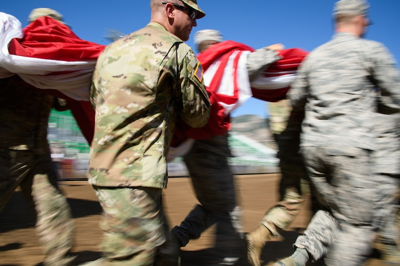 Hill Air Force Base Airmen alongside other military members and first responders serving in Utah carry an American flag during Patriot Night at the Ogden Pioneer Days Rodeo in Ogden, Utah, July 22, 2019.