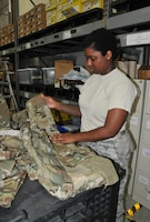 Airman Basic Damaja Prince, 403rd LRS supply apprentice, folds and separates the new Operational Camouflage Pattern uniforms by size in order to fill uniform orders as required. The new uniforms will be mandatory wear by April 1, 2021, with deploying members being the first to receive the uniform. (U.S. Air Force photo by Jessica L. Kendziorek)