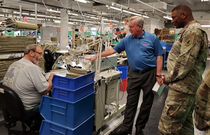 Mike Gilliam, CEO/President of San Antonio Lighthouse for the Blind & Vision Impaired, gives Maj. Gen. Patrick D. Sergeant a tour of the facility while machine operator John, with very little vision, sews the zipper onto the inclement weather pant for the Army.