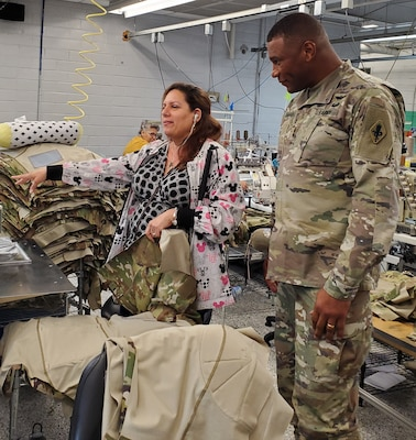 Maj. Gen. Patrick D. Sargent (right), commanding general of the U.S. Army Medical Department Center and School Health Readiness Center of Excellence, visits with Roberta, a machine operator, while she sews the sleeve of an Army Combat Shirt. Roberta has very little vision and is in the Lighthouse Choir.