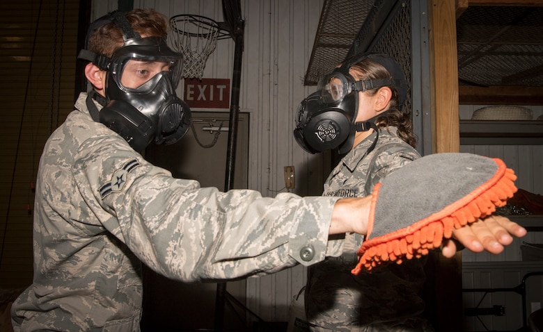 Airman 1st Class Jesse Booher, a 6th Logistics Readiness Squadron petroleum, oils and lubricants fuels technician, goes through a decontamination line with Airman 1st Class Alexes Shelton, a 6th Force Support Squadron food services apprentice, during deployment readiness training, at MacDill Air Force Base, Fla., July 25, 2019.