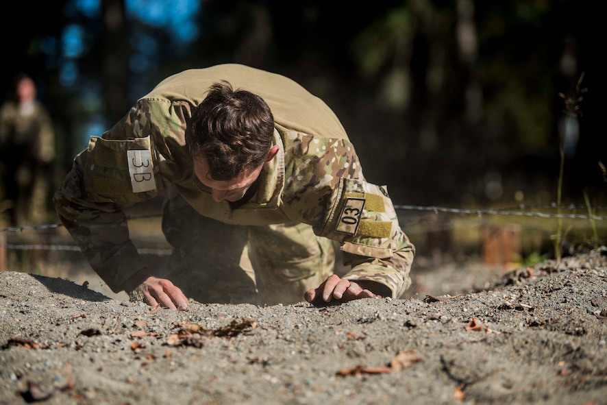 A U.S. Air Force Tactical Air Control Party (TACP) Airman assigned to the 5th Air Support Operations Squadron, Joint Base Lewis-McChord (JBLM), Wash., low crawls through sand during the 2019 Lightning Challenge at JBLM, Wash., July 29, 2019.