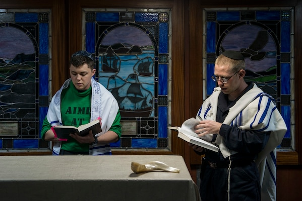 Sailors from Newton, Iowa, read from prayer books during the Rosh Hashanah service in the chapel of the Nimitz-class aircraft carrier USS Ronald Reagan.