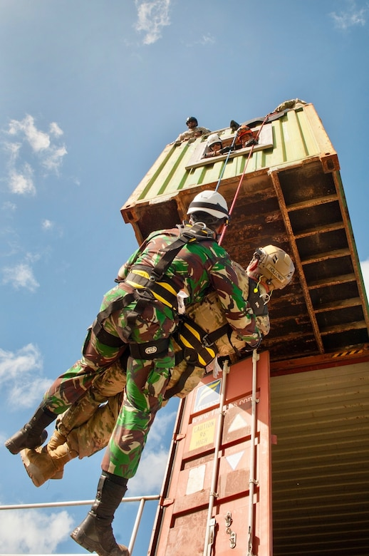 An Indonesian soldier assists a simulated wounded Hawaii Army National Guardsman as he repels from a second story building during a Combined - Multinational Task Force [CTF 501] search and extraction training scenario on July 18, 2019 at Kalaeloa Urban Search and Rescue Training area, Hawaii. Service members from the Philippines, Indonesia, Bangladesh, Vietnam, Oregon Air National Guard traveled to Hawaii as part of a State Partnership Program training event.