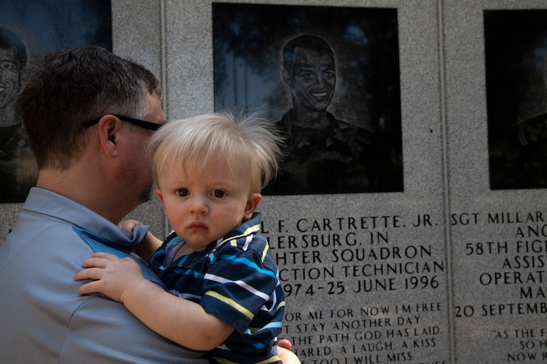 Jerry Adams and child take a moment of silence in front of Senior Airman Earl Cartrette Jr.'s memorial at Eglin Air Force Base, Florida, on July 29, 2019. Sally Adams, Jerry's wife and sister of Cartrette, was adopted when she was two weeks old and spent her life searching for her biological family. Upon finding out her brother had died in the 1996 Khobar Towers attack, she and her family made the visit to Eglin to see the memorial. (U.S. Air Force photo by Senior Airman Cassidy Woody)