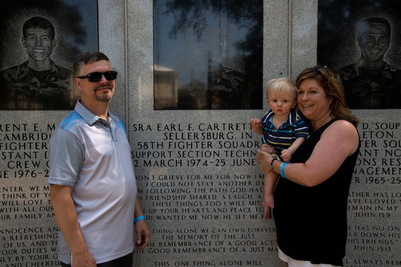 Jerry and Sally Adams pose in front of Senior Airman Earl Cartrette Jr.'s memorial with their child at Eglin Air Force Base, Florida, on July 29, 2019. Sally was adopted when she was two weeks old and spent her life searching for her biological family. Upon finding out her brother had died in the 1996 Khobar Towers attack she and her family made the visit to Eglin to see the memorial. (U.S. Air Force photo by Senior Airman Cassidy Woody)