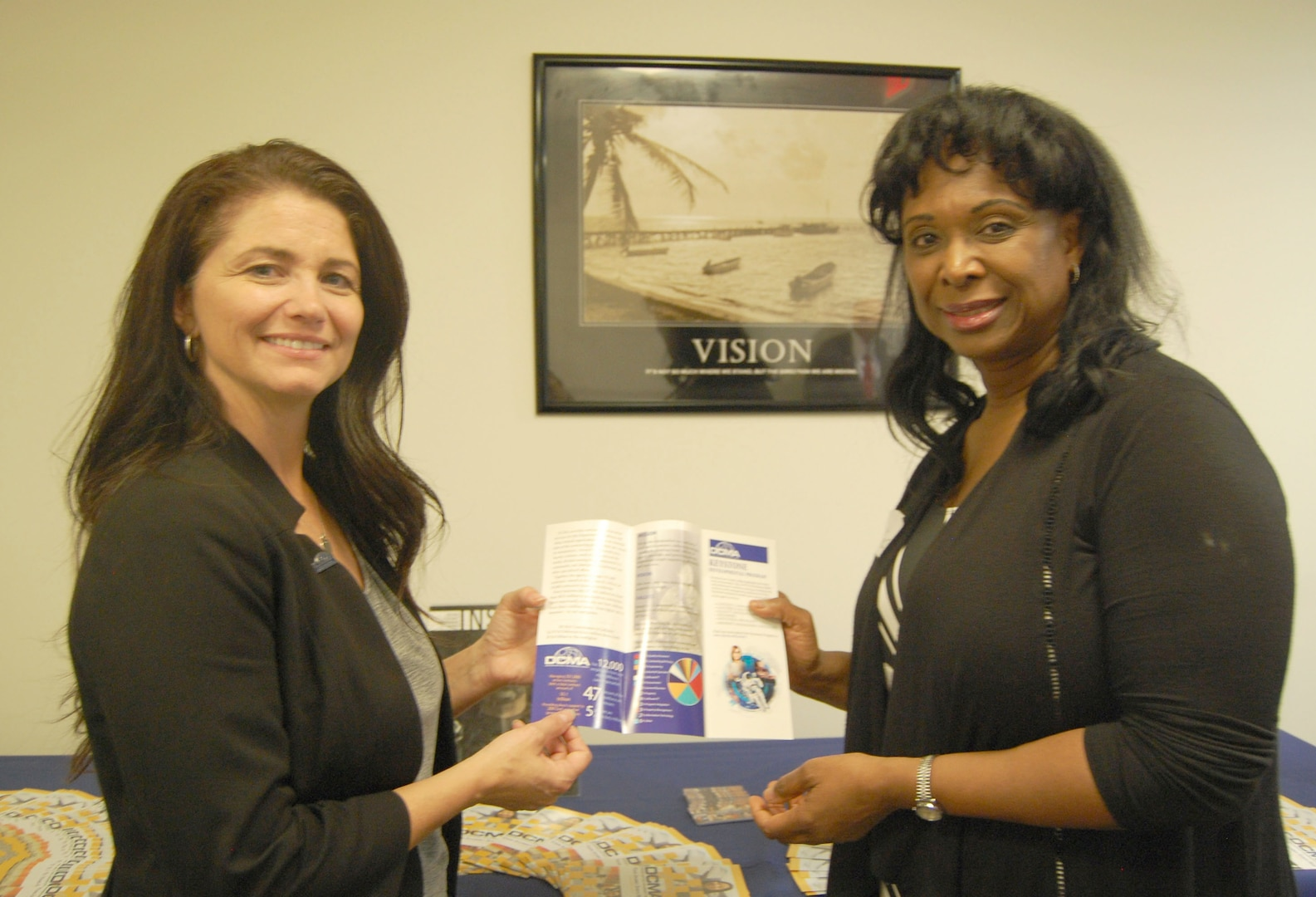 Photo of two female employees reviewing a DCMA brochure
