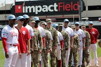 Army Reserve Soldiers assigned to the 85th U.S. Army Reserve Support Command headquarters pause for a photo with players from the American Association of Independent Professional Baseball's Chicago Dogs baseball team, July 28, 2019, at Impact Field in Rosemont, Illinois during a home game there against the Cleburne Railroaders.