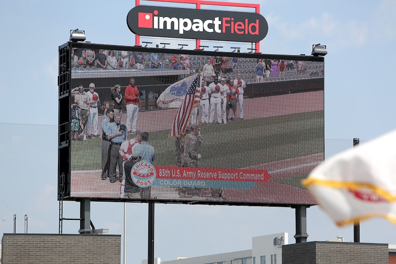 An Army Reserve color guard team, assigned to the 85th U.S. Army Reserve Support Command headquarters, are highlighted on a Jumbotron at the American Association of Independent Professional Baseball's Chicago Dogs baseball home game, July 28, 2019, at Impact Field in Rosemont, Illinois against the Cleburne Railroaders.