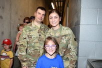 U.S. Army Reserve Capt. Michael Ariola, left, and Sgt. Maribel Meraz, assigned to the 85th U.S. Army Reserve Support Command headquarters, pause for a photo with Mae Gossage, 8, who wanted to meet Meraz and stated that she did not know that women can join the Army, during the American Association of Independent Professional Baseball's Chicago Dogs baseball home game, July 28, 2019, at Impact Field in Rosemont, Illinois against the Cleburne Railroaders.