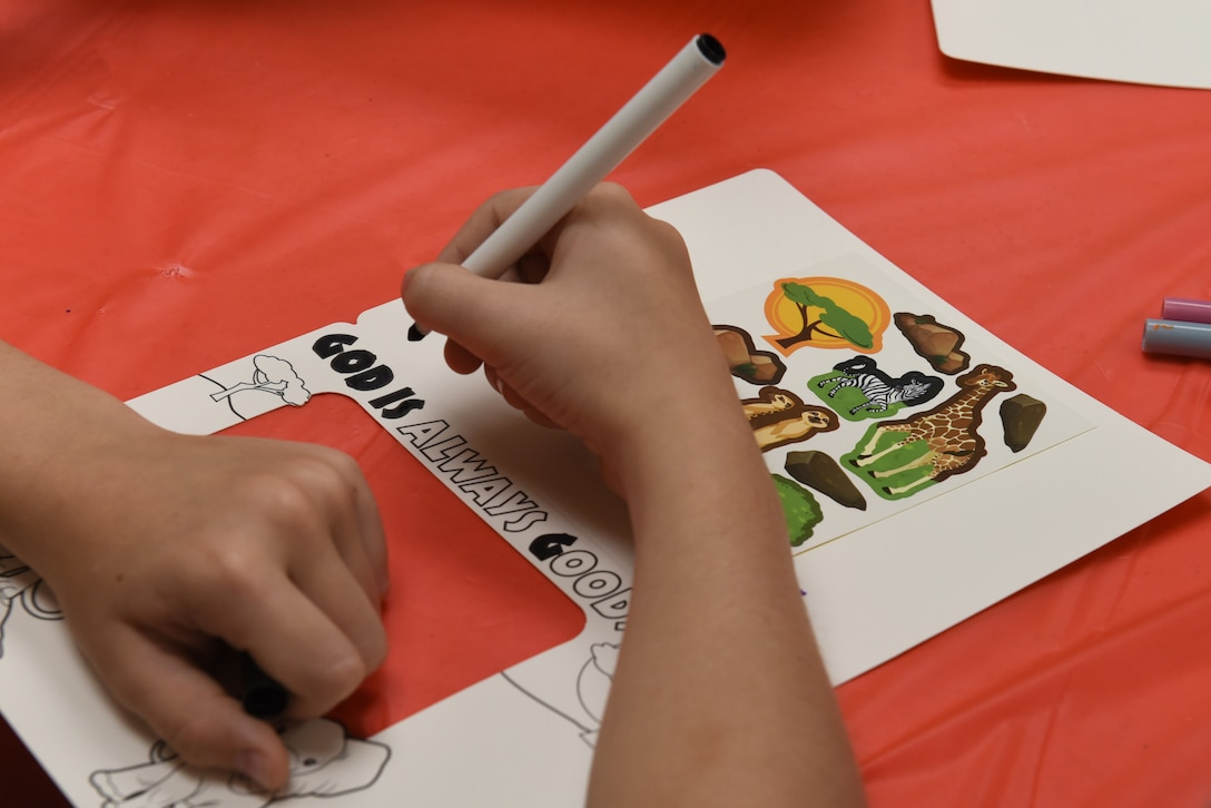 A child colors at Vacation Bible School at the Chapel Community Center at Ellsworth Air Force Base, S.D., July 21, 2019. The Chaplain Corps, in partnership with a youth group from the Immanuel Christian Reformed Church from Orange City, Iowa, hosted the weeklong event for children to play and learn lessons about faith and the struggles they may face in life. (U.S. Air Force photo by Airman Quentin K. Marx)