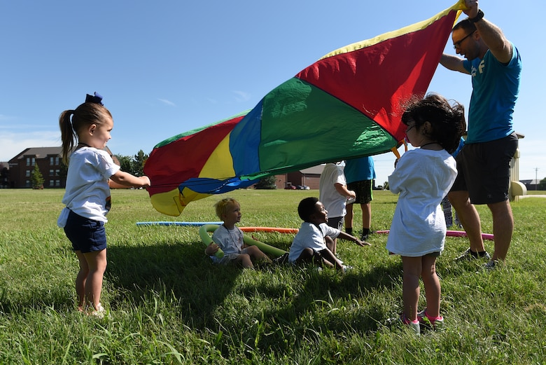 Children play with a parachute at Vacation Bible School at the Chapel Community Center at Ellsworth Air Force Base, S.D., July 21, 2019. Approximately 70 children, ages 6 through 12, participated in the weeklong event, which had songs, bible lessons, cinema time, and outdoor activities. (U.S. Air Force photo by Airman Quentin K. Marx)