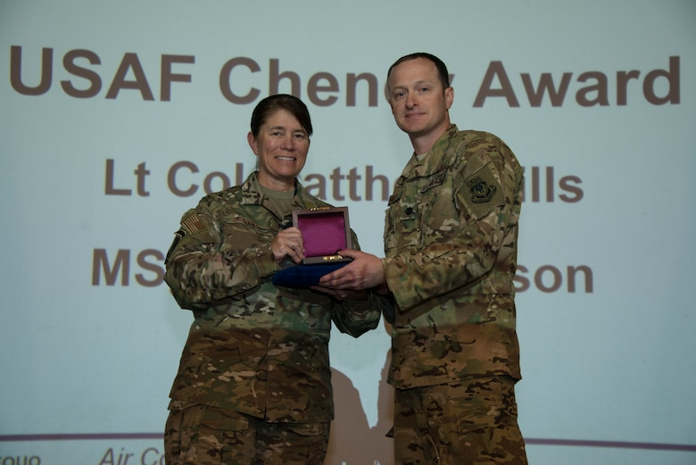 Two people holding an award in front of a screen.