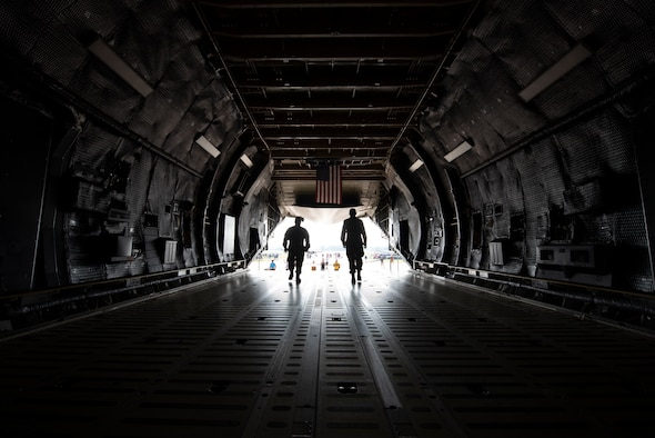 U.S. Air Force Tech. Sgt. Audy Cayanan, 60th Aerial Port Squadron transportation craftsman, left, and Senior Airman Marcus Bueno, 60th APS transportation journeyman, walk toward an exit on a C-5M Super Galaxy July 27, 2019, at Wittman Regional Airport in Oshkosh, Wisconsin. The C-5 crew went to EAA AirVenture 2019 where more than 500,000 aviation enthusiasts from 80 countries gathered at the air show to celebrate the past, present and future in the world of aviation. (U.S. Air Force photo by Senior Airman Jonathon Carnell)