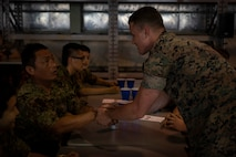 A U.S. Marine shakes hands with a soldier of the Japanese Ground Self-Defense Force during a Mess Night July 22, 2019 at Camp Fuji. The event was put together to build a stronger alliance through a U.S. Marine Corps tradition. (U.S. Marine Corps photo by Lance Cpl. Brennan J. Beauton)