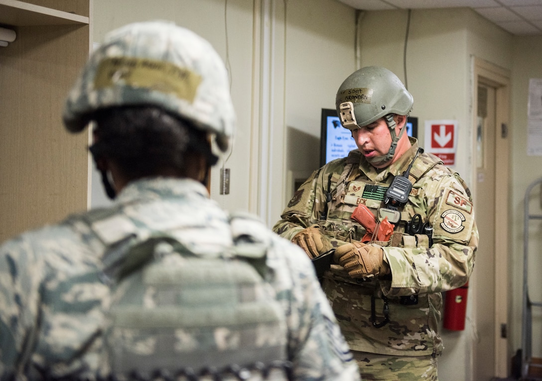 U.S. Air Force Staff Sgt. Brandan Eck (right), and Tech. Sgt. Ashlin Thomas (left), 8th Security Forces Squadron members, search the personal effects of a simulated active shooter during an exercise at Kunsan Air Base, Republic of Korea, July 23, 2019. 8th SFS routinely trains to respond to a variety of threats. (U.S. Air Force photo by Senior Airman Stefan Alvarez)