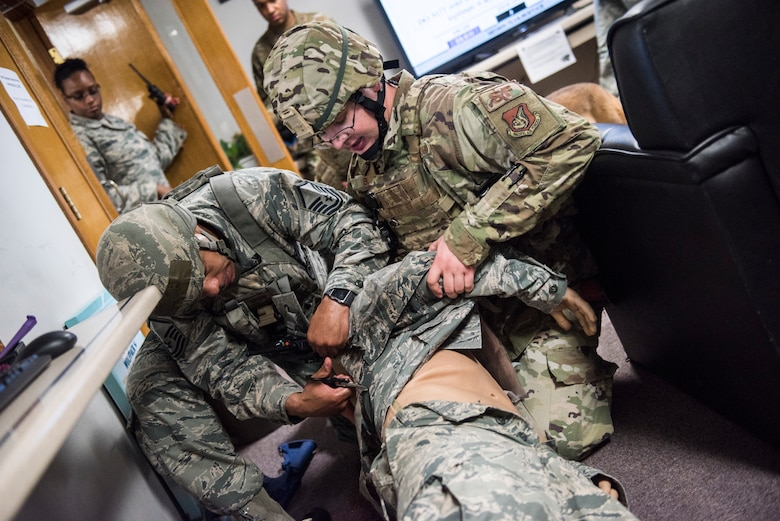 U.S. Air Force Master Sgt. Marquis Wilson (right), and Staff Sgt. Charles Billups (left), 8th Security Forces Squadron members, perform first aid on a simulated victim during an exercise at Kunsan Air Base, Republic of Korea, July 23, 2019. Once alerted, 8th SFS responded with precision to a simulated active shooter call, neutralized the simulated threat and secured the area. (U.S. Air Force photo by Senior Airman Stefan Alvarez)