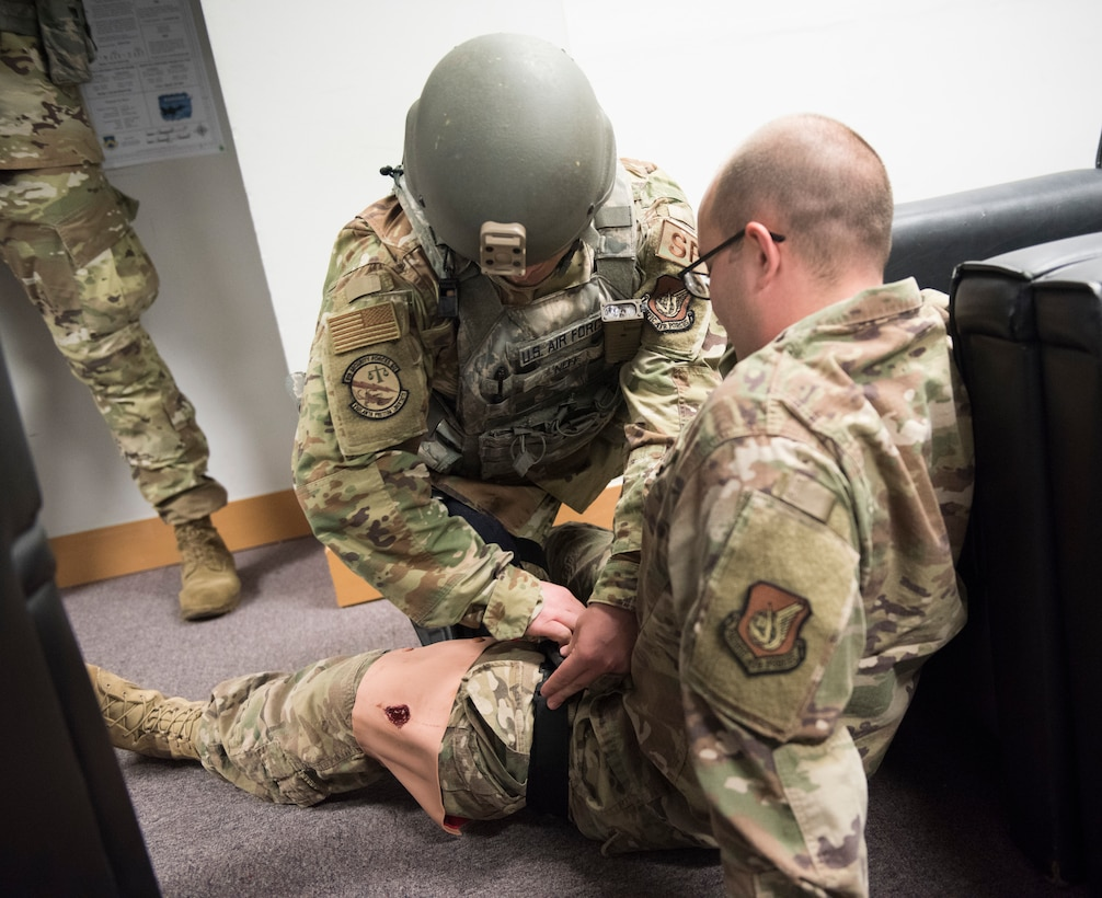 U.S. Air Force Staff Sgt. Bryce Neff, 8th Security Forces Squadron member, performs first aid on a simulated victim during an exercise at Kunsan Air Base, Republic of Korea, July 23, 2019. Once alerted, 8th SFS responded with precision to a simulated active shooter call, neutralized the simulated threat and secured the area. (U.S. Air Force photo by Senior Airman Stefan Alvarez)