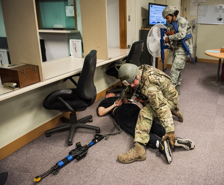 U.S. Air Force Staff Sgt. Brandan Eck (left), and Tech. Sgt. Ashlin Thomas (right), 8th Security Forces Squadron members, search a simulated active shooter during an exercise at Kunsan Air Base, Republic of Korea, July 23, 2019. 8th SFS routinely trains to respond to a variety of threats. (U.S. Air Force photo by Senior Airman Stefan Alvarez)