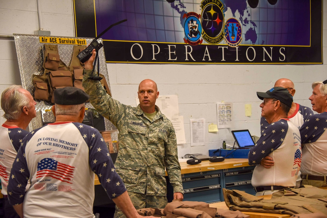 Tech. Sgt. Michael Bullister holds a radio up during a briefing to Vietnam veterans